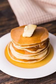 Goldene pfannkuchen mit butter und warmem ahornsirup.