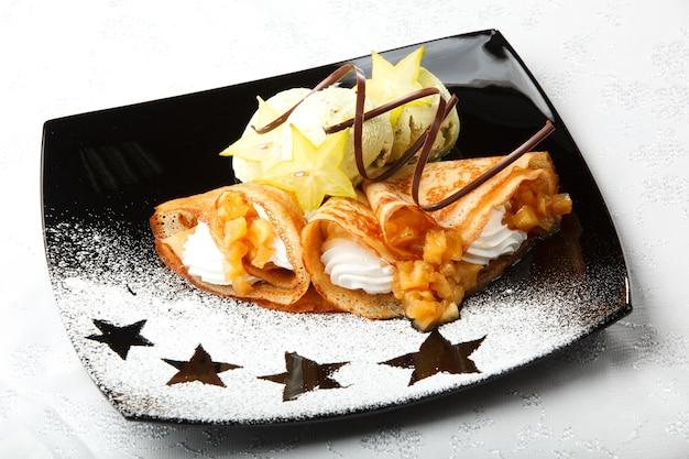 Goldene pfannkuchen mit carambola und schlagsahne