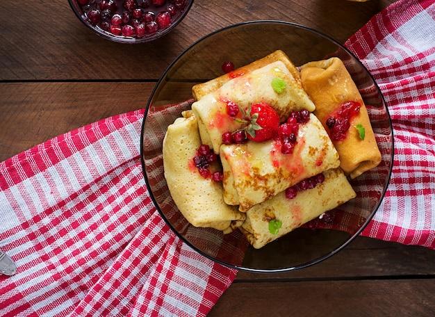 Goldene pfannkuchen mit preiselbeermarmelade und honig im rustikalen stil. ansicht von oben