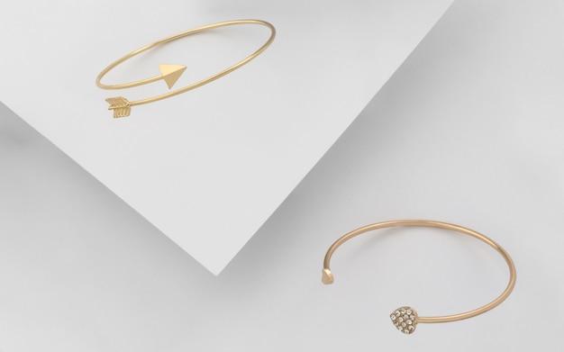 Goldene pfeil- und herzformarmbänder auf weißem hintergrund. goldene armbänder des modernen designs auf weißem papierhintergrund