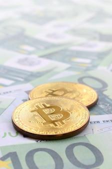 Goldene physische bitcoins liegt auf einer reihe grüner währungen