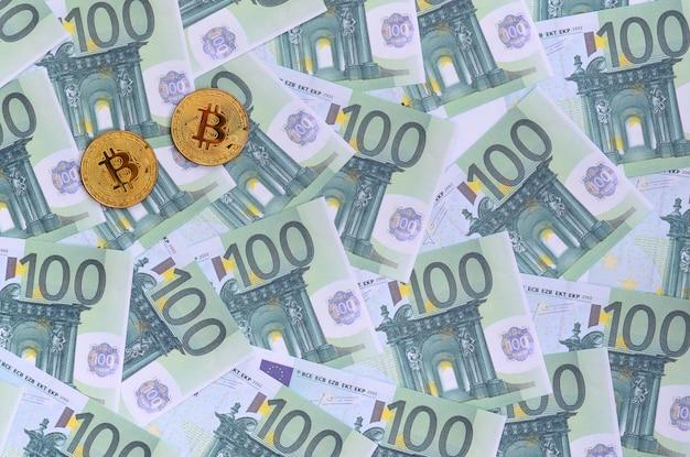 Goldene physische bitcoins liegt auf einer reihe grüner währungsbezeichnungen von 100 euro. viel geld bildet einen unendlichen haufen