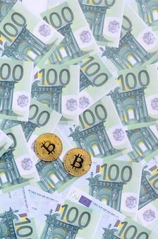 Goldene physische bitcoins liegt auf einer reihe grüner währungsbezeichnungen von 100 euro
