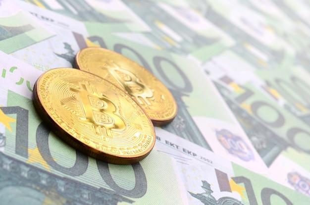 Goldene physische bitcoins liegt auf einer reihe grüner währungsbezeichnungen von 100 euro.