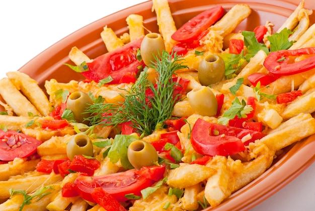Goldene pommes frites kartoffeln mit tomaten und oliven auf weißem hintergrund
