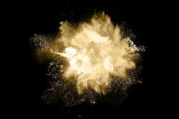 Goldene pulverexplosion auf schwarzem hintergrund.