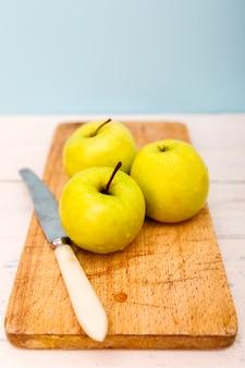 Goldene reife äpfel auf schneidebrett mit messer.