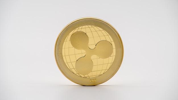 Goldene ripplecoin-währung des physischen metalls auf weißer wand. neues weltweites virtuelles internetgeld. digital ripple coin cyberspace, kryptowährung xrp. gute investition zukünftige online-zahlung