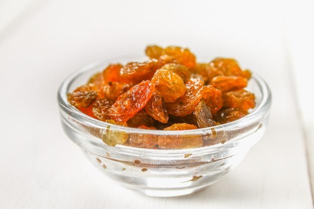Goldene rosinen aus getrockneten trauben in einer glasschüssel auf entlassung auf einem weißen holztisch von brettern.