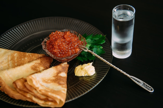 Goldene russische pfannkuchen mit rotem kaviar und butter in der transparenten platte nahe dem glas des eiswodkas lokalisiert auf schwarz. restaurant der nationalen küche.