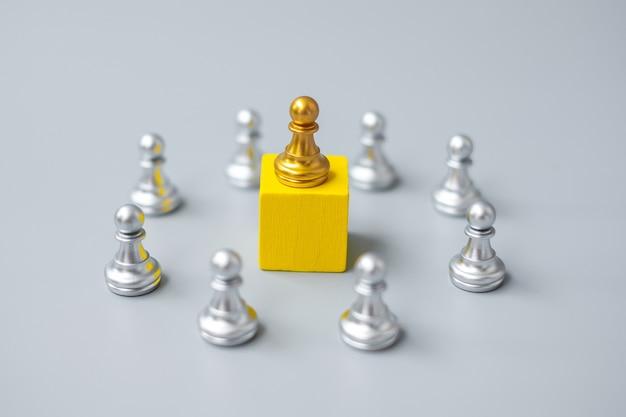 Goldene schachfiguren oder führergeschäftsmann mit kreis silberner männer. sieg, führung, geschäftserfolg, team und teamwork-konzept