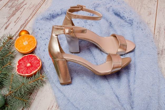 Goldene schuhe auf blauer strickjacke, pampelmuse, orange und fichtenzweig. mode-konzept
