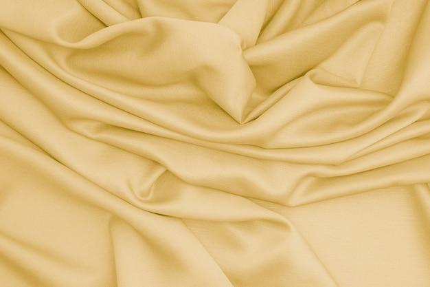 Goldene seidenstoff-satinoberfläche mit weichen wellen aus goldenem stofftexturhintergrund