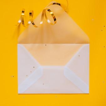 Goldene sterndekorationen des feiertags und offener transparenter mattumschlag für ihren text auf gelbem hintergrund. planungskonzept
