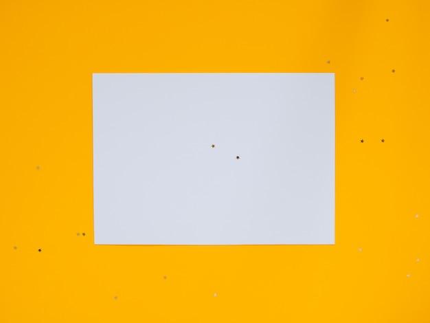 Goldene sterndekorationen des feiertags und weißer sauberer freier raum für ihren text auf gelbem hintergrund