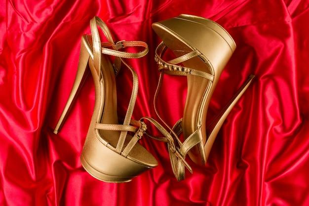 Goldene streifen high heels auf rotem satin
