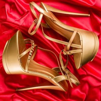 Goldene streifen hohe absätze auf rotem satinhintergrund - bild