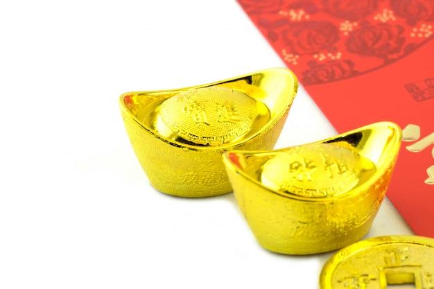 Goldene sycee und rote umschläge mit geldspenden für junge familienmitglieder.