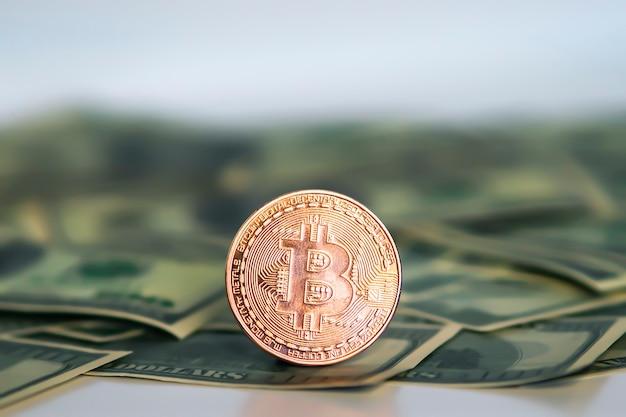 Goldene symbolische münze bitcoin auf banknoten von dollar. tauschen sie bitcoin-bargeld gegen einen dollar. kryptowährung auf us-dollar-scheinen. digitale moderne zahlungsmethode.