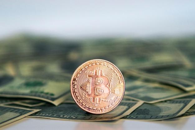 Goldene symbolische münze bitcoin auf banknoten von dollar. tauschen sie bitcoin-bargeld gegen einen dollar