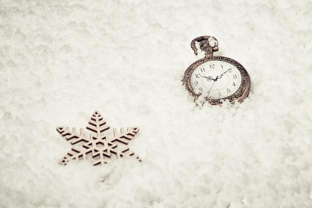 Goldene taschenuhr der weinlese und spielzeugschneeflocken auf schnee