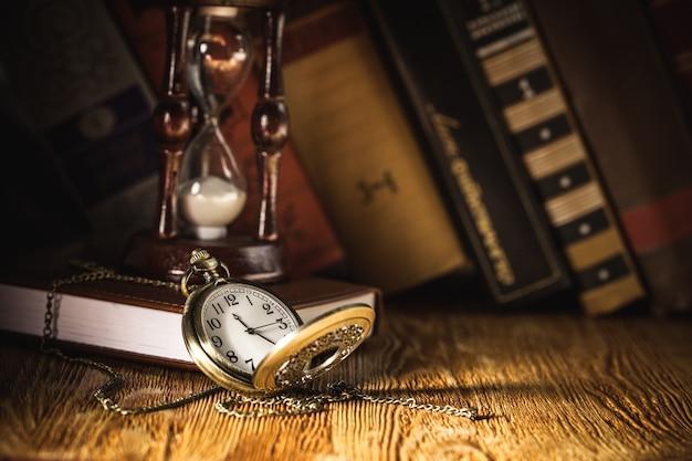 Goldene taschenuhr und alte bücher mit vintage-seiten