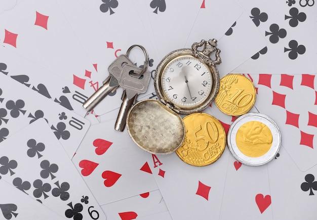 Goldene taschenuhr und münzen, schlüssel auf spielkarten. alles steht auf dem spiel