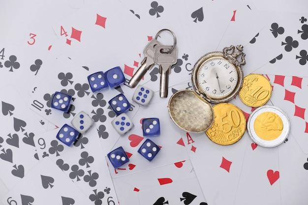 Goldene taschenuhr und münzen, schlüssel, würfel auf spielkarten. alles steht auf dem spiel