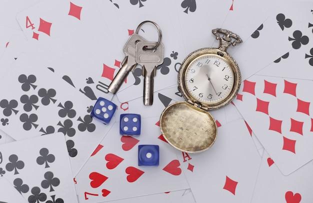 Goldene taschenuhr und schlüssel, würfel auf spielkarten. alles steht auf dem spiel