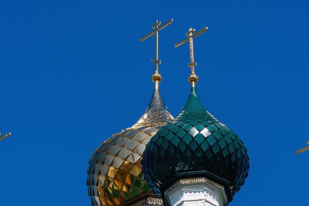 Goldene und grüne kuppeln mit kreuzen der russisch-orthodoxen kirche