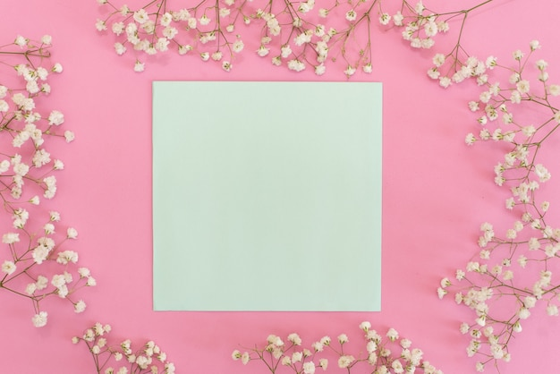Goldene und rosa konfettis, die aus weißem umschlag auf pastellrosahintergrund heraus gießen.