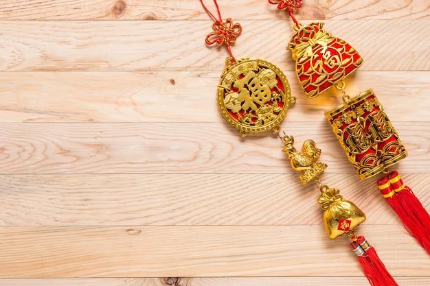 Goldene und rote chinesische dekoration des neuen jahres der draufsicht auf hölzernem hintergrund
