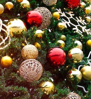 Goldene und rote dekorationen spielzeugkugeln hängen am weihnachtsbaum.