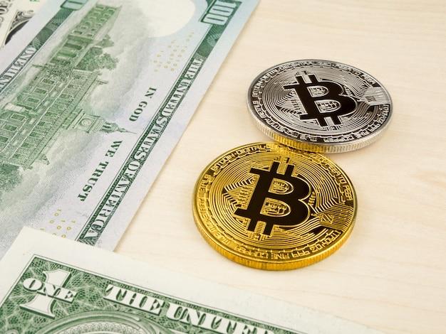 Goldene und silberne bitcoin münze auf us-dollars schließen oben.