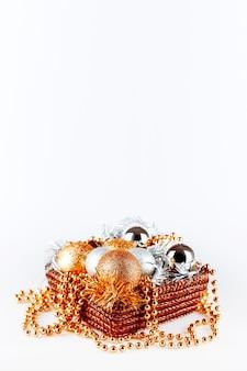 Goldene und silberne kugeln in box mit lametta und perlen. weihnachten und dekorationen in gesponnenem kasten auf weiß.