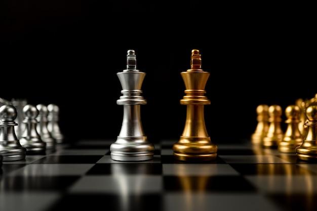 Goldene und silberne schachkönigsfiguren laden sie von angesicht zu angesicht ein und es gibt schachfiguren im hintergrund. konzept des wettbewerbs, der führung und der geschäftsvision für einen sieg in planspielen