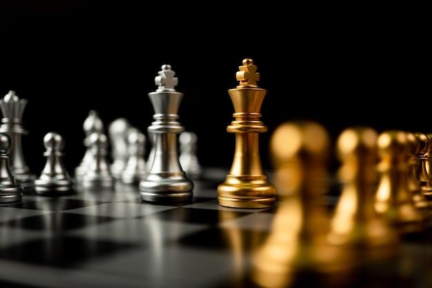 Goldene und silberne schachkönigsteile laden sie von angesicht zu angesicht ein und im hintergrund befinden sich schachfiguren.