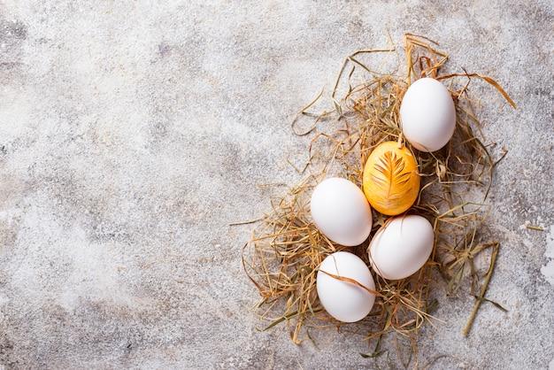 Goldene und weiße eier des osterhuhns