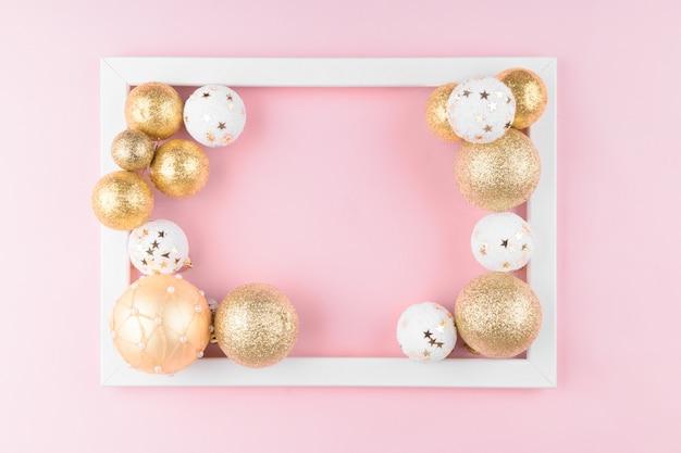 Goldene und weiße weihnachtskugeln und bildfotokunstrahmen auf stilvollem rosa festlichem elegantem hintergrund