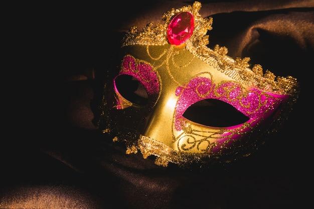 Goldene venezianische maske mit einem dunklen hintergrund