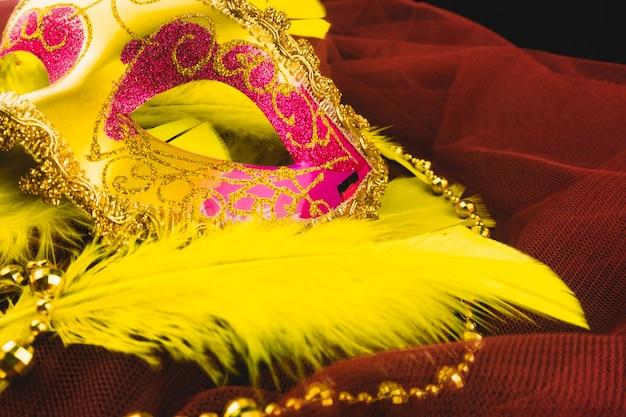 Goldene venezianische maske mit federn auf einem roten stoff
