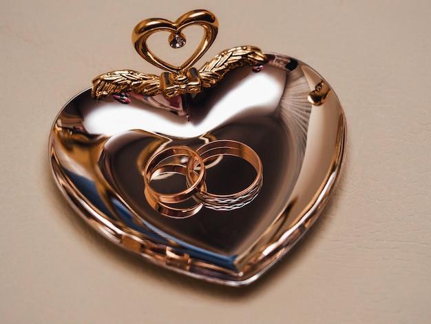 Goldene verlobungsringe auf einer dekorativen platte