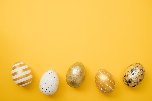 Goldene verzierte eier ostern auf gelbem hintergrund. frohe ostern-karte