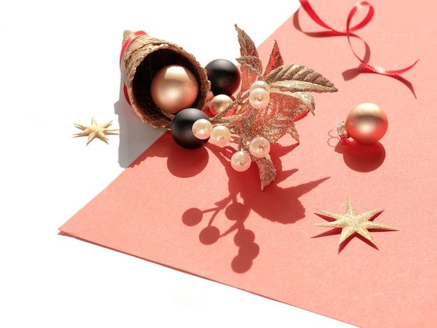Goldene waffeleistüte mit weihnachtsgold und schwarzen kugeln, zweig mit beeren, sternen und roten bändern auf orangefarbenem papier