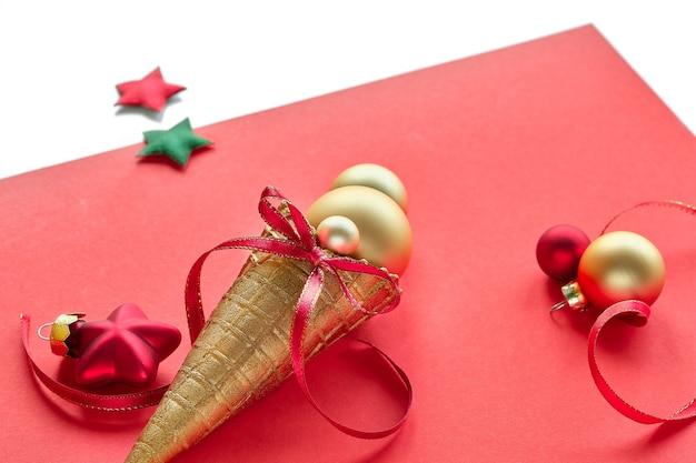 Goldene waffeleistüte mit weihnachtsgoldkugeln, sternen und roten bändern