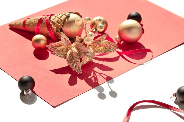Goldene waffeleistüte, weihnachtsgold und schwarze kugeln und zweig mit beeren auf rosa papier warnen