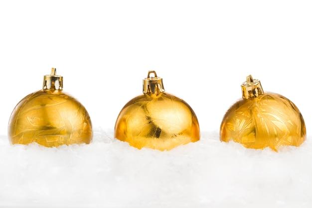 Goldene weihnachtsbälle auf dem eis und schnee lokalisiert auf weißem backgro