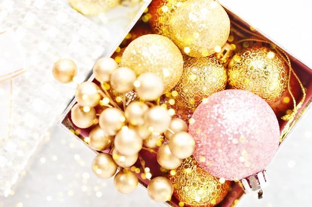 Goldene weihnachtsbälle auf einem hellen hintergrund. ansicht von oben. weihnachten hintergrund.