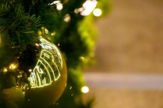 Goldene weihnachtsbälle der nahaufnahme verziert auf kiefer am weihnachtstag mit bokeh der geführten beleuchtung und des undeutlichen hintergrundes.