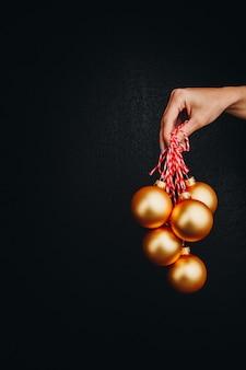 Goldene weihnachtsbälle in der hand der frau lokalisiert auf schwarzem hintergrund